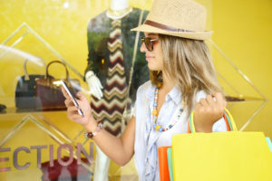 Young woman with shopping bags texting close to a retail display